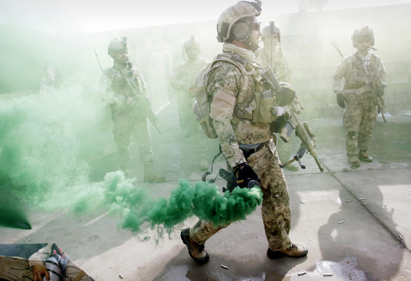 In this Monday, Jan. 14, 2013 photo, a member of Afghan special forces carries a smoke bomb during a training exercise on the outskirts of Kabul, Afghanistan. Afghanistan's army is training female special forces to take part in night raids against insurgents despite cultural taboos as foreign combat troops take the backseat ahead of their eventual departure at the end of 2014. In a country where women traditionally are expected to stay home, their participation in the special forces is breaking new ground in ultraconservative Afghanistan. (AP Photo/Musadeq Sadeq)