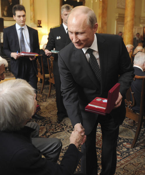 Russian President Vladimir Putin works together with Britain's Prime Minister David Cameron, not pictured, to award Russian Ushakov medals to Arctic Convoy Veterans, during a ceremony inside No 10 Downing street in London, Sunday June 16, 2013. The Russian Ushakov medals were awarded as a symbol to show Russia's gratitude to the brave survivors of the Arctic convoys who battled storms, bombers and U-boats to ferry war supplies to Russia as they were fighting the Nazis during the second World War. (AP Photo / Anthony Devlin)