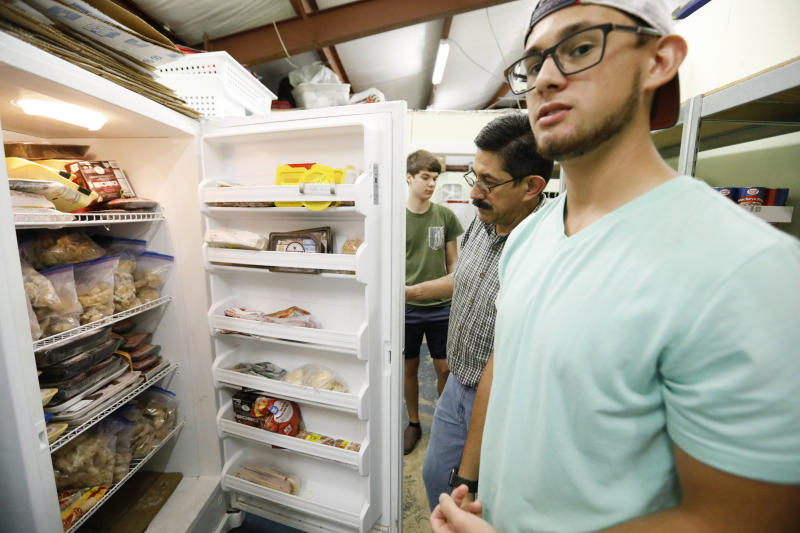 In this Thursday, Aug. 8, 2019 photo, while his father, Pastor Hugo Villegas inspects the freezer, Pablo Villegas, right, says the pantry at the Carlisle Crisis Center in Forest, Miss., has a limited amount of perishable foods, courtesy of the immediate community, as well as contributions from individuals as far away as Jackson, and help from some social agencies and civic groups.  The center, a ministry of Scott County Baptist Association, says they will need more food items to help out the families affected by the fallout of Wednesday's raid by U.S. immigration officials at poultry plants Koch Foods and PH Foods in neighboring Morton. The raids were part of a large-scale operation targeting owners as well as undocumented employees. (AP Photo/Rogelio V. Solis)