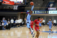 Villanova's Brandon Slater, left, goes up for a dunk past St. John's Julian Champagnie during the first half of an NCAA college basketball game, Tuesday, Feb. 23, 2021, in Villanova, Pa. (AP Photo/Matt Slocum)