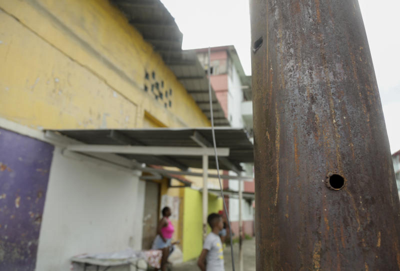 """In this Dec. 1, 2019, bullets holes pierce a street lamp pole, which residents say were made during the night of the 1989 U.S. invasion, in the El Chorrillo neighborhood where former Gen. Manuel A. Noriega operated his headquarters and is an area that was targeted for attack in Panama City. Today this area still has desolate parts where residents say bombs fell and where graffiti with phrases like """"Forbidden to forget"""" and """"Dec. 20, national mourning"""" cover the walls. (AP Photo/Arnulfo Franco)"""