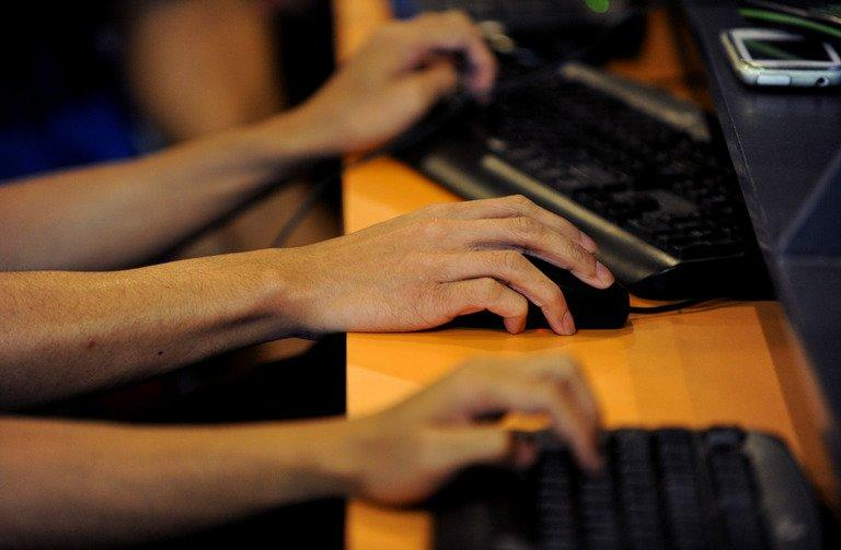 Customers use computers at an Internet cafe in Manila on February 1, 2013