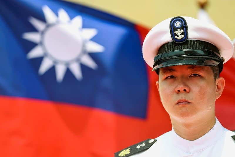 """FILE PHOTO: A Taiwan Navy honor guard looks on in front of a Taiwan flag during the launch ceremony for Taiwan Navy's domestically built amphibious transport dock """"Yushan"""" in Kaohsiung"""