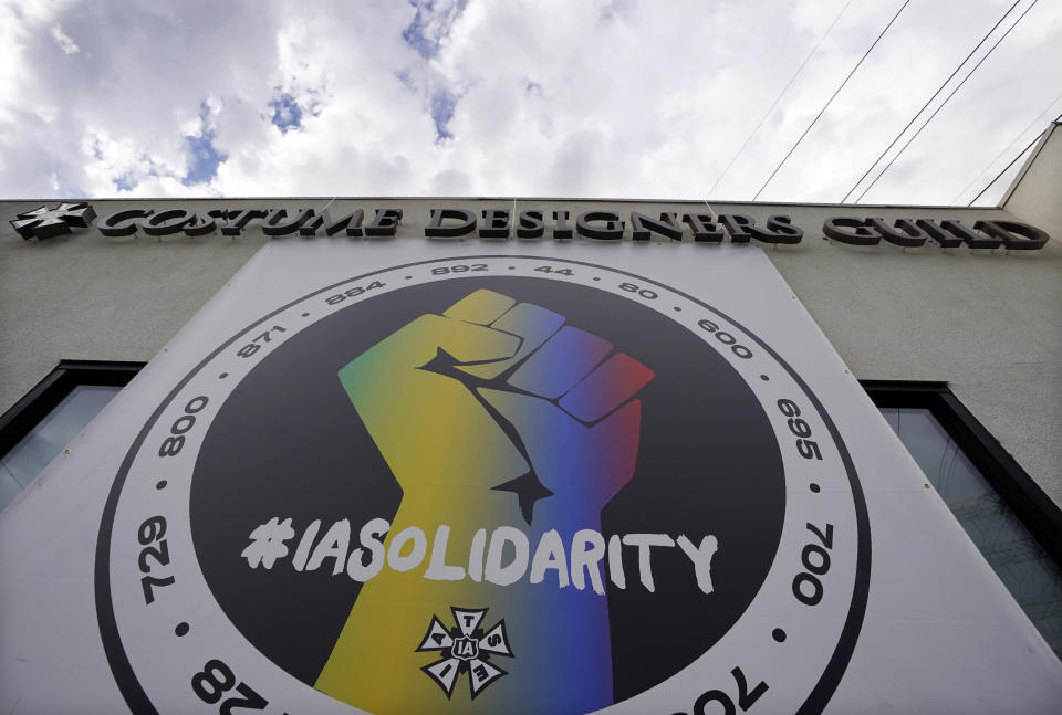 A poster advocating union solidarity hangs from a Costume Designers Guild office building, Monday, Oct. 4, 2021, in Burbank, Calif. The International Alliance of Theatrical Stage Employees (IATSE) overwhelmingly voted to authorize a strike for the first time in its 128-year history. (AP Photo/Chris Pizzello)