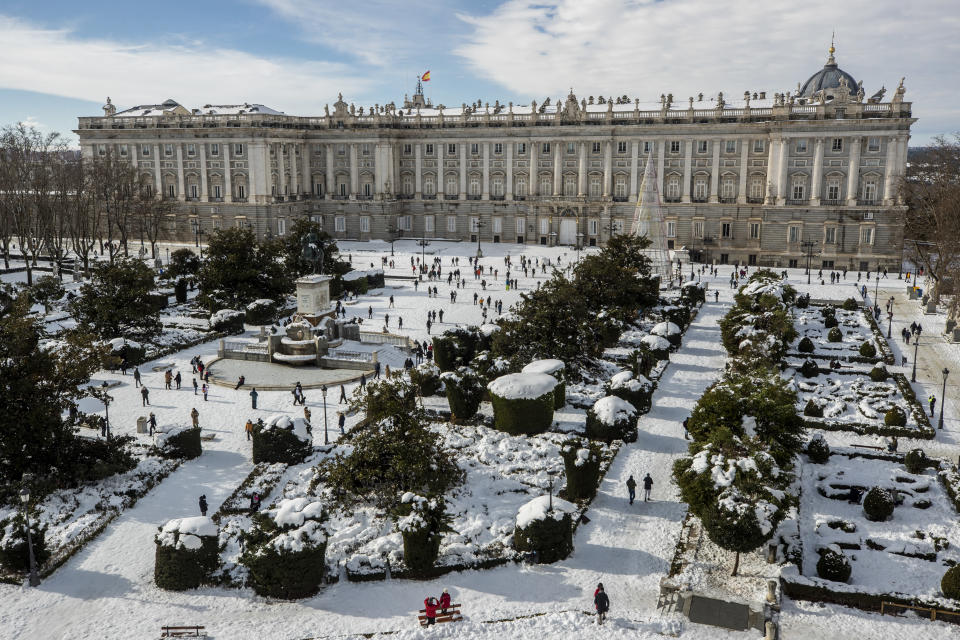 A view of Oriente square covered with snow with the Royal Palace in front in downtown Madrid, Spain, Sunday, Jan. 10, 2021. A large part of central Spain including the capital of Madrid are slowly clearing snow after the country's worst snowstorm in recent memory. (AP Photo/Manu Fernandez)