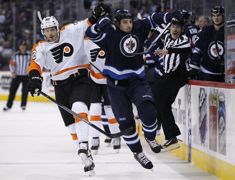 Philadelphia Flyers' Mark Streit (32) and Winnipeg Jets' Chris Thorburn (22) race for the puck during second-period NHL hockey game action in Winnipeg , Manitoba, Friday, Nov. 15, 2013. (AP Photo/The Canadian Press, John Woods)