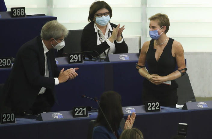 European Commissioner for Economy Paolo Gentiloni, left, speaks with Tokyo 2020 Paralympic gold medallist Beatrice Vio, right, at the European Parliament in Strasbourg, France, Wednesday, Sept. 15, 2021. The European Union announced Wednesday it is committing 200 million more coronavirus vaccine doses to Africa to help curb the COVID-19 pandemic on a global scale. (Yves Herman, Pool via AP)