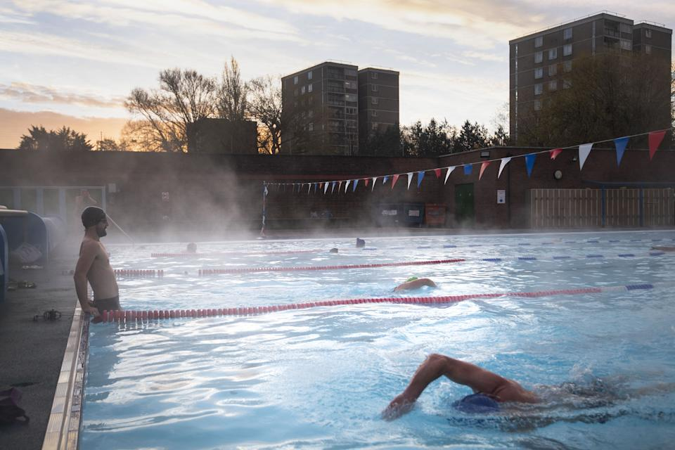Early morning swimmers during sunrise at Charlton Lido in Hornfair Park, London, on its first day of reopening after the second national lockdown ended and England enters a strengthened tiered system of regional coronavirus restrictions.