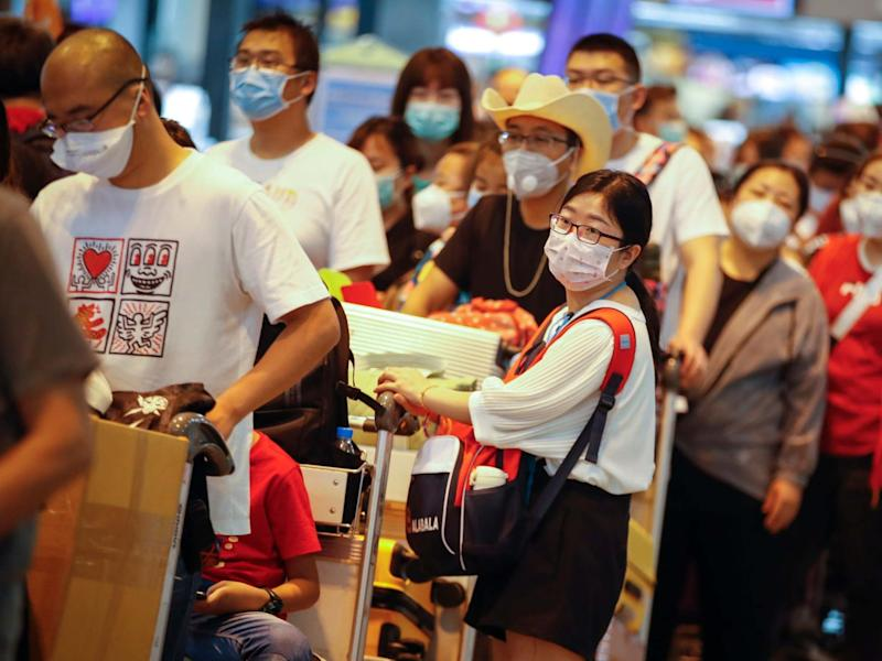 Chinese tourists wearing protective masks wait in line at Don Mueang airport in Bangkok, Thailand: EPA