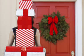 Woman holding stack of wrapped boxes, presents, or gifts. Presents cover her face as she stands in front of a red door with gree