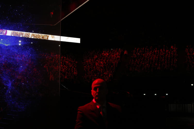 A security guard stands during the final of League of Legends tournament between Team G2 Esports and Team FunPlus Phoenix, in Paris, Sunday, Nov. 10, 2019. The biggest e-sports event of the year saw a Chinese team, FunPlus Phoenix, crowned as world champions of the video game League of Legends. Thousands of fans packed a Paris arena for the event, which marked another step forward for the growing esports business. (AP Photo/Thibault Camus)