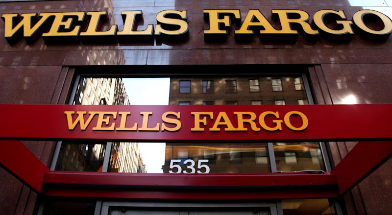 FILE - In this May 6, 2012, file photo, a Wells Fargo sign is displayed at a branch in New York.  Wells Fargo is reporting higher earnings and revenue for the third quarter, thanks to higher fees a rise in trading revenue. (AP Photo/CX Matiash, File)