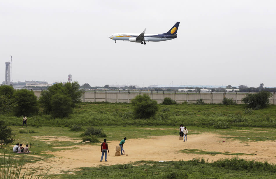 People play cricket as a Jet Airways passenger plane prepares to land at the Indira Gandhi International Airport in New Delhi July 29, 2013. India's foreign investment regulator gave conditional approval on Monday to a $379 million deal by Abu Dhabi's Etihad Airways to buy a stake in Jet Airways (India) Ltd, paving the way for more acquisitions in the domestic aviation sector. REUTERS/Adnan Abidi (INDIA - Tags: BUSINESS TRANSPORT SPORT CRICKET)
