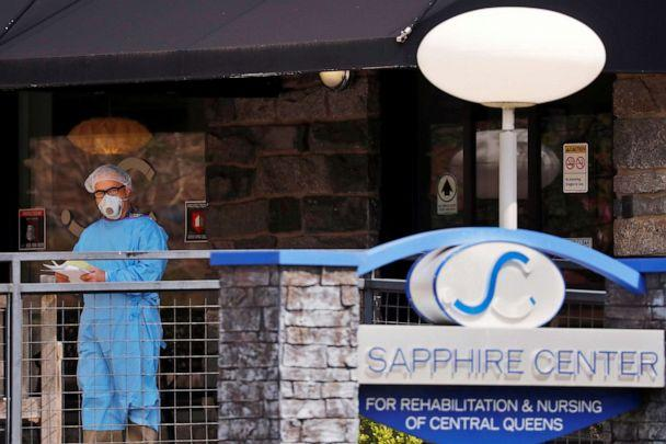 PHOTO: A man wearing PPE stands behind a sign for the Sapphire Center nursing home after reports of a number of deaths there came to light during an ongoing outbreak of coronavirus  (COVID-19) in the Brooklyn borough of New York, April 17, 2020. (Lucas Jackson/Reuters, FILE)