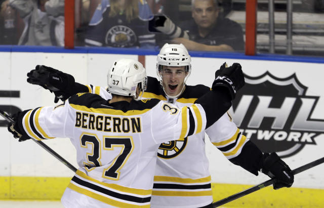 Boston Bruins right wing Reilly Smith (18) is congratulated by teammate Patrice Bergeron (37) after Smith scored the game-winning goal, 3-2, against the Florida Panthers in the third period of an NHL hockey game, Thursday, Oct. 17, 2013, in Sunrise, Fla. (AP Photo/Alan Diaz)