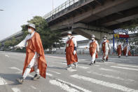 Buddhist monks walk along a road in Seoul, South Korea, Tuesday, Oct. 27, 2020. About 100 monks and believers marched the 500-kilometer (310-mile) pilgrimage to wish for the country to overcome the coronavirus. (AP Photo/Lee Jin-man)
