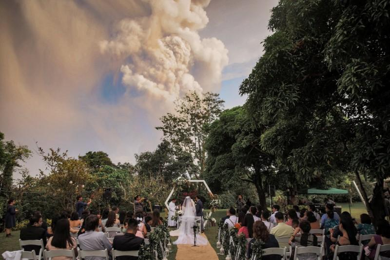 Social media image of people attending a wedding ceremony as Taal Volcano sends out a column of ash in the background in Alfonso, Cavite, Philippines