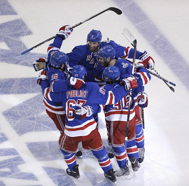 New York Rangers left wing Benoit Pouliot (67) celebrates with teammates after scoring in the first period during Game 4 of the NHL hockey Stanley Cup Final against the Los Angeles Kings, Wednesday, June 11, 2014, in New York. (AP Photo/Seth Wenig)