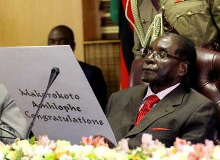 FILE PHOTO:  Zimbabwe's President Robert Mugabe reads a card during his 93rd birthday celebrations in Harare