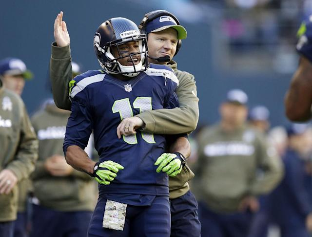 Seattle Seahawks' wide receiver Percy Harvin (11) is hugged on the sideline by Seattle Seahawks offensive coordinator Darrell Bevell during an NFL football game against the Minnesota Vikings, Sunday, Nov. 17, 2013, in Seattle. The game was Harvin's first back on the field following hip surgery earlier in the year and his first against the Vikings since he was traded to the Seahawks. The Seahawks won 41-20. (AP Photo/Ted S. Warren)