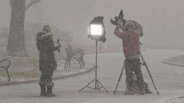 PHOTO: Reporters produce a television report in a snow squall outside the New York state Capitol, Wednesday, Jan. 20, 2021, in Albany, N.Y. Joe Biden was inaugurated as President on Wednesday in Washington. (Hans Pennink/AP)
