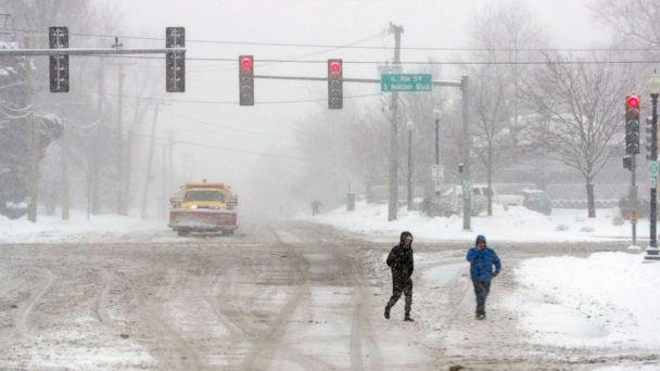 PHOTO: Two unidentified men cross the street after heavy snow fall on Jan. 26, 2021, in West Chicago, U.S. (Brian Hill/AP)