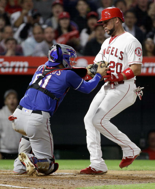 Los Angeles Angels' Jose Fernandez, right, is tagged out at home by Texas Rangers catcher Robinson Chirinos while trying to score on a ball hit by Shohei Ohtani during the fourth inning of a baseball game in Anaheim, Calif., Tuesday, Sept. 25, 2018. (AP Photo/Chris Carlson)