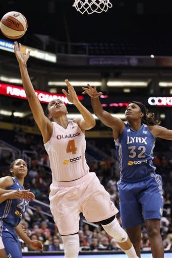 Phoenix Mercury's Candice Dupree (4) gets past Minnesota Lynx's Rebekkah Brunson (32) and Maya Moore (23) to score during the first half of a WNBA basketball game Friday, Sept. 21, 2012, in Phoenix.(AP Photo/Ross D. Franklin)