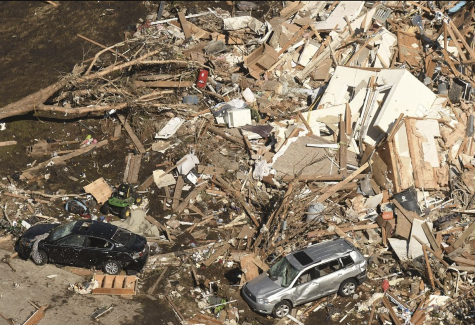 Houses flattened by the tornado and two crumpled cars.