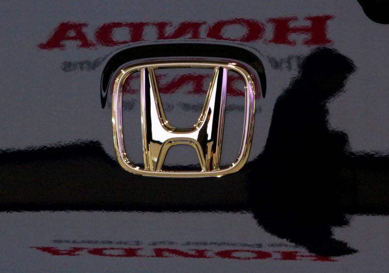 Visitor and logo of Honda Motor Co are reflected on a Honda car at company headquarters in Tokyo