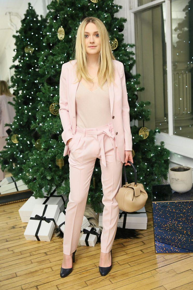 Dakota Fanning poses in front of the Christmas tree in a look that's more May Day than Christmas Day. (Photo: Getty Images)