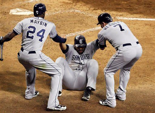 San Diego Padres' Carlos Quentin, center, gets help getting up off the ground from teammates Cameron Maybin (24) and Chase Headley (7) after scoring a run against the Arizona Diamondbacks during the sixth inning of a baseball game on Saturday, Aug. 25, 2012, in Phoenix. (AP Photo/Ross D. Franklin)
