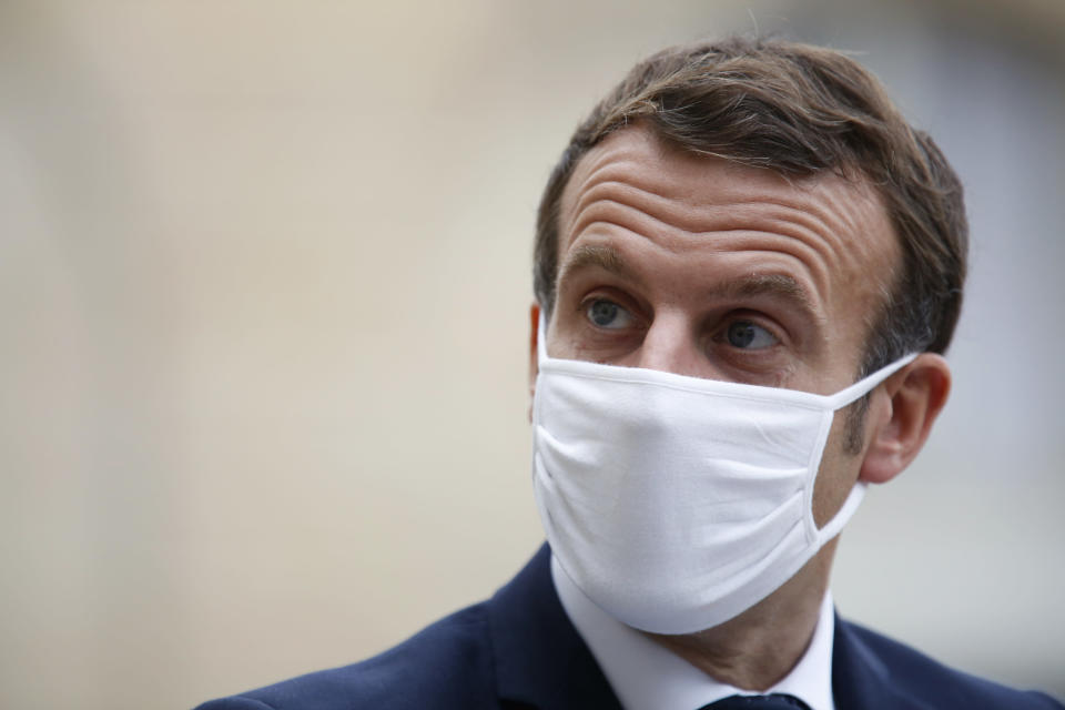 France's President Emmanuel Macron wears a mask during a speech of Estonia's Prime Minister Juri Ratas, at the Elysee Palace, in Paris, Wednesday, Oct. 28, 2020. France is bracing for a potential new lockdown as the president prepares a televised address Wednesday aimed at stopping a fast-rising tide of virus patients filling French hospitals and a growing daily death toll. French markets opened lower on expectations that President Emmanuel Macron will announce some kind of lockdown Wednesday. (AP Photo/Thibault Camus)