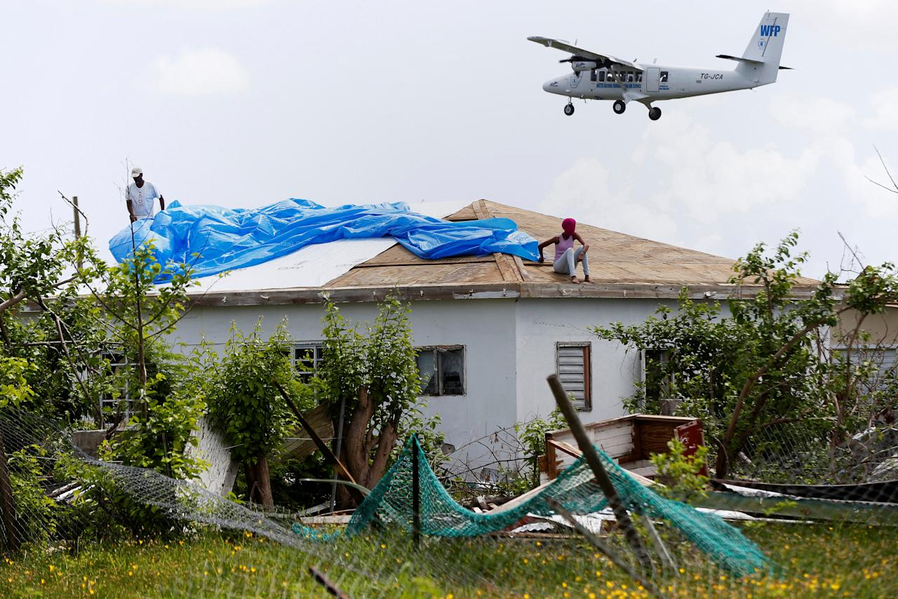 <p>Devon Warner and his daughter Che Niesha work on the roof of a home at Codrington on the island of Barbuda just after a month after Hurricane Irma struck the Caribbean islands of Antigua and Barbuda, October 7, 2017. REUTERS/Shannon Stapleton </p>