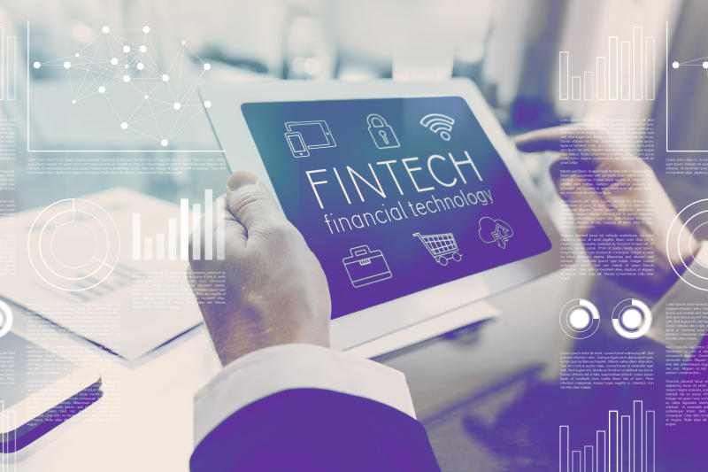 A pair of hands holding a tablet with a screen that reads fintech financial technology.