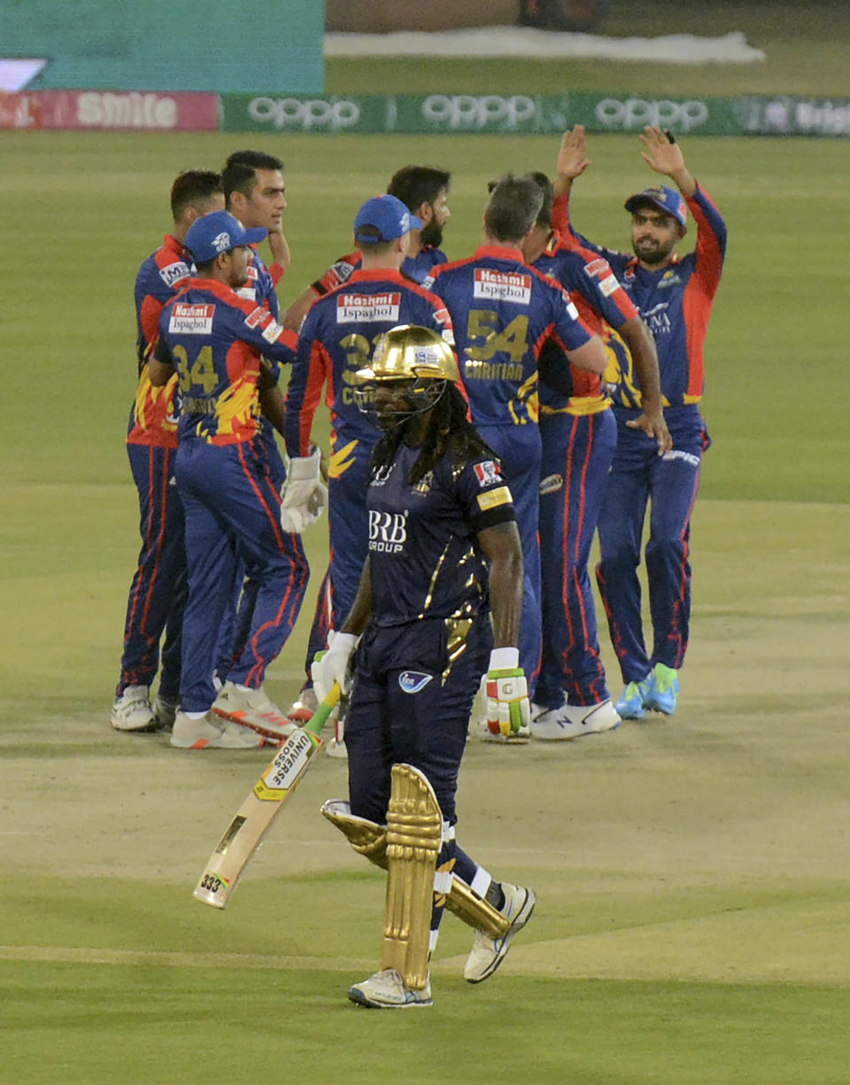 Quetta Gladiators Chris Gayle, front, walks back, while Karachi Kings players celebrate his dismissal during a Pakistan Super League T20 cricket match between Karachi Kings and Quetta Gladiators at National Stadium, in Karachi, Pakistan, Saturday, Feb. 20 2021. (AP Photo/Fareed Khan)