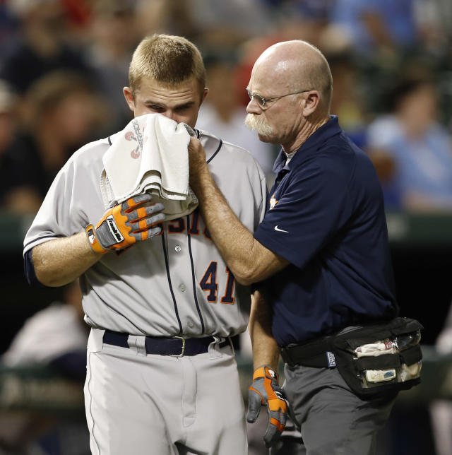 Houston Astros' Max Stassi (41) is checked on by trainer Rex Jones after getting hit in the face by a pitch thrown by Texas Rangers reliever Tanner Scheppers during the eighth inning of a baseball game, Wednesday, Aug. 21, 2013, in Arlington, Texas. (AP Photo/Jim Cowsert)