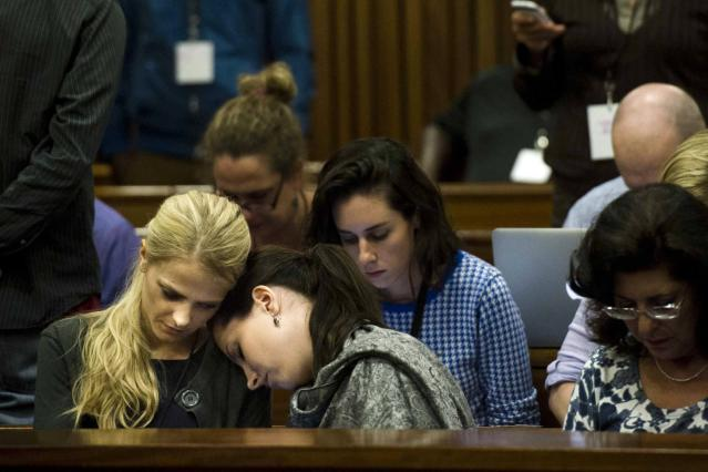 Aimee Pistorius, sister of Olympic and Paralympic track star Oscar, rests her head on an unidentified woman's shoulder during the fifth day of his trial for the murder of his girlfriend Reeva Steenkamp at the North Gauteng High Court in Pretoria, March 7, 2014. REUTERS/Theana Breugem/Pool (SOUTH AFRICA - Tags: SPORT ATHLETICS CRIME LAW)