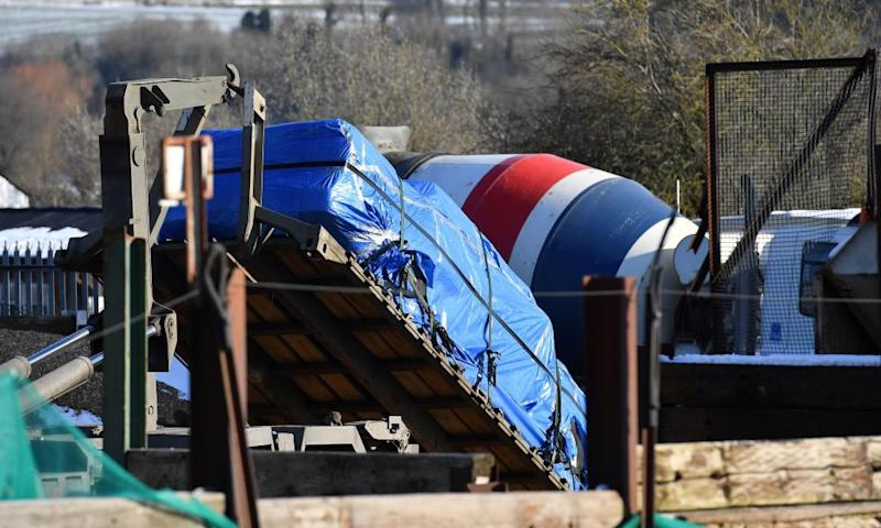 A vehicle, covered in tarpaulin, is loaded on to the back of a British army lorry at a cement plant in the village of Durrington.