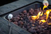"""<p>The primary decision you need to make when shopping for a fire pit is whether you want a wood-burning or gas pit.</p><p><strong>Wood burning fire pits</strong> use wood logs, wood pellets, charcoal, or some combination thereof, and you make them the way you would an open bonfire. However, they're generally safer and more convenient than bonfires because they're deep enough to prevent embers from flying everywhere, designed to give off less smoke, and many have ashtrays in the base for convenient cleanup. Some also have internal fans to keep the fire going. You should opt for a wood-burning fire if you love that campfire smell, are interested in cooking outdoors, and want to generate a lot of heat. The drawbacks are the ash cleanup, the fuel maintenance, and the potential for smokiness, as well as the potential fire hazard from embers.</p><p><strong>Gas fire pits</strong> use propane or natural gas to generate a """"clean"""" fire, with no embers, ash, or cleanup. They're generally safer and more consistent than wood-burning fires because there's no fire hazard from embers, and they can be switched on with the flip or a switch or by pressing a button. They often have different heat and flame height levels. Gas fire pits are great to use for elegant outdoor tables or patios, or when camping somewhere where wood fires are banned or inconvenient. However, gas fires aren't ideal for cooking because of the potential mess, they don't provide you with the smell of a campfire, and you'll need to be able to store the propane tank somewhere. Tanks and gas lines also need to be carefully inspected and maintained to prevent leaks.</p>"""