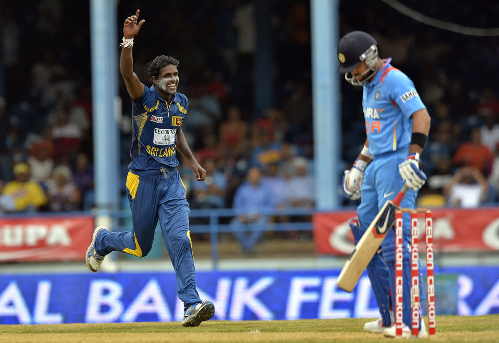 Sri Lankan bowler Shaminda Eranga (L) celebrates dismissing Indian batsman Virat Kohli (R) during the final match of the Tri-Nation series between India and Sri Lanka at the Queen's Park Oval stadium in Port of Spain on July 11, 2013. Sri Lanka have scored 201/10. AFP PHOTO/Jewel Samad