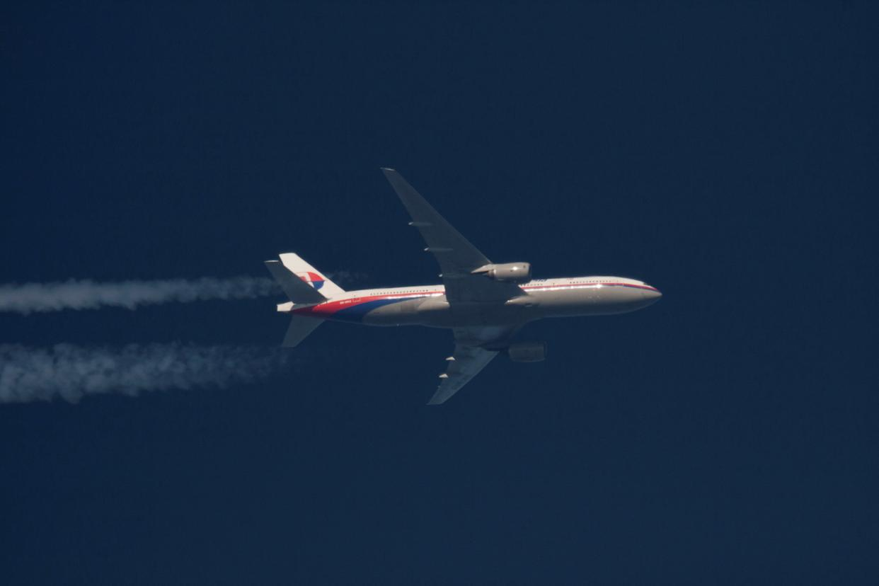 FILE PHOTO: Malaysian Airlines Boeing 777-200ER with the registration number 9M-MRO flies over Poland February 5, 2014. The aircraft flying as MH370 disappeared on March 8, 2014, less than an hour into a flight from Kuala Lumpur to Beijing. REUTERS/Tomasz Bartkowiak/File Photo
