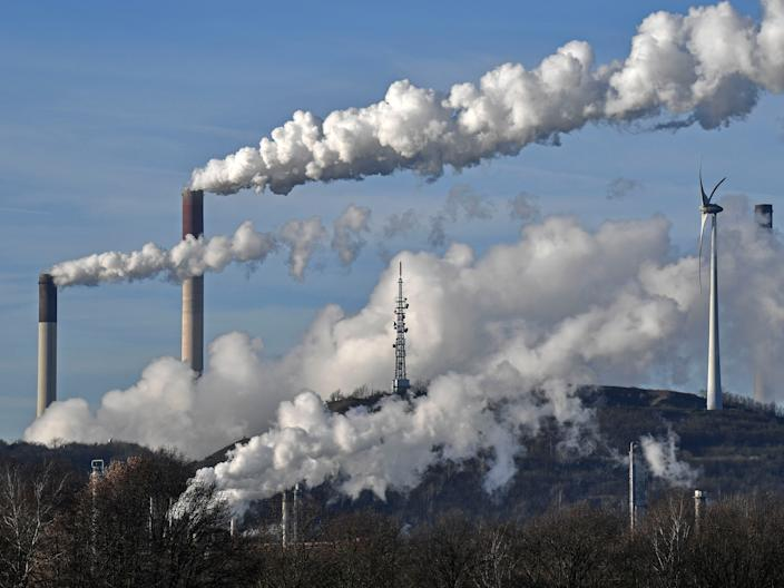 """FILE - This Jan. 16, 2020 file photo shows a Uniper energy company coal-fired power plant and a BP refinery beside a wind generator in Gelsenkirchen, Germany. The world hit another new record high for heat-trapping carbon dioxide in the atmosphere, despite reduced emissions because of the coronavirus pandemic, scientists announced Thursday, June 4, 2020. (AP Photo/Martin Meissner) <p class=""""copyright"""">Associated Press</p>"""
