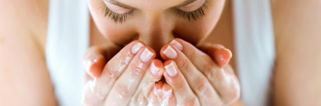 a woman is washing her face