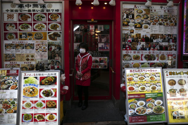 In this Feb. 13, 2020, photo, a restaurant worker wearing a mask stands in front of a Chinese restaurant clustered with photos of the menu items in Yokohama's Chinatown, near Tokyo. A top Olympic official made clear Friday the 2020 Games in Tokyo will not be cancelled despite the virus that has spread from China. (AP Photo/Jae C. Hong)