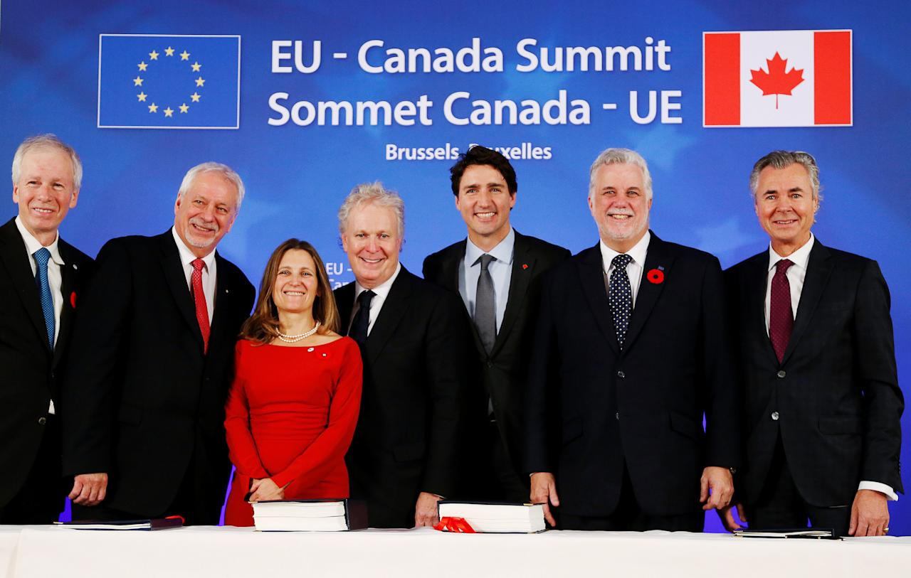 (L-R) Canada's Foreign Minister Stephane Dion, Quebec's former Premier Pierre-Marc Johnson, Canada's International Trade Minister Chrystia Freeland, Quebec's former Premier Jean Charest, Canada's Prime Minister Justin Trudeau, Quebec's Premier Philippe Couillard and Canada's CETA Envoy Pierre Pettigrew pose after signing the Comprehensive Economic and Trade Agreement (CETA), at the European Council in Brussels, Belgium, October 30, 2016.  REUTERS/Francois Lenoir