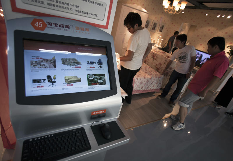 In this Friday May 27, 2011, photo, a computer screen display various furniture items with selling price while Chinese shop inside the newly opened Taobao Mall in Beijing, China. China's e-commerce giant is stepping up its heated rivalry with bricks-and-mortar retailers with the launch of a five-story home furnishings showroom in Beijing. Alibaba Group's Taobao, an Internet platform through which an estimated 3 percent of all retail sales in China pass, opened the showroom Friday for customers to try out sofas, tables and other big-ticket items before placing an order with one of its merchants. (AP Photo/Andy Wong)