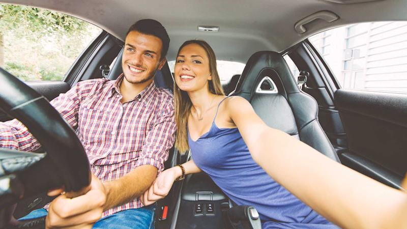 Young couple taking selfie with phone while driving