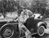 <p>Clark Gable sits in his car chatting to Greta Garbo while stroking a german shepherd dog in a scene from the film Susan Lenox (Her Fall And Rise).</p>