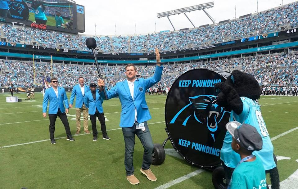 """Former Carolina Panthers player Jordan Gross prepares to hit the """"Keep Pounding"""" drum, joined by Steve Smith, Sr, Wesley Walls, and Jake Delhomme prior to a game in 2019."""